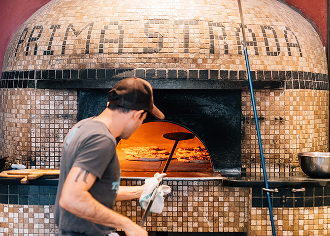 Enjoy a wood-fired pizza atr Prima Strada
